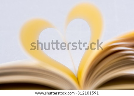 Heart Shaped Book. Symmetrical book page in heart shape, focus on foreground. - stock photo