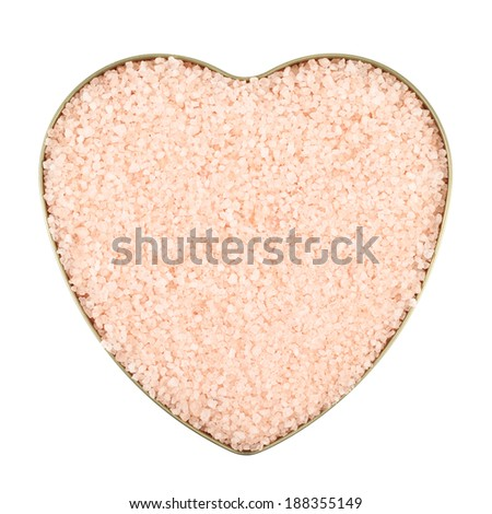 Heart shaped box filled with pink colored salt crystals, isolated over the white background - stock photo