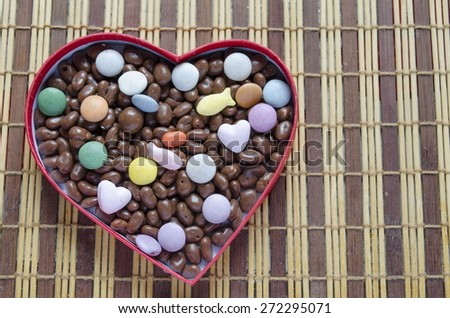 Heart shaped box filled with small chocolates balls on the wooden bamboo table