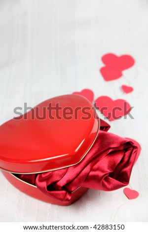 Heart shaped box with a red satin gift. Is it lingerie? Nightie? Or maybe a scarf?