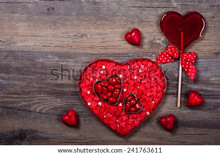 Heart shaped box with Valentine's Day candies on the vintage wooden background - stock photo