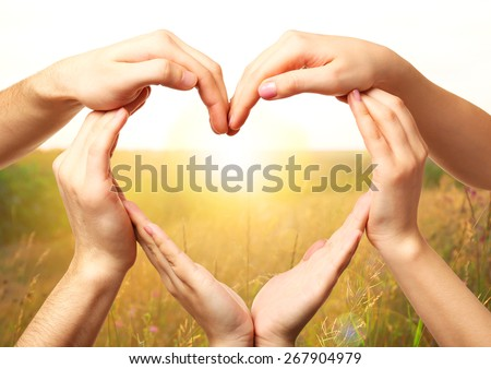 Heart shaped by hands on nature background - stock photo