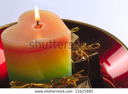 heart shaped candle and gold presents in a red glass bowl
