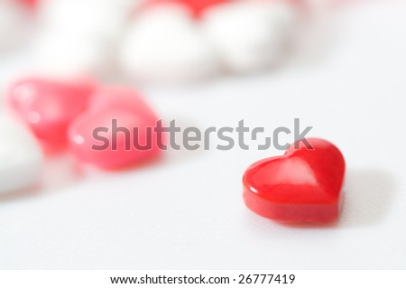 Heart shaped candy in foreground with blurry candies in background. On white background. Candies are red, pink and white...