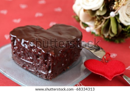 Heart shaped chocolate cake with heart decoration and bouquet - stock photo