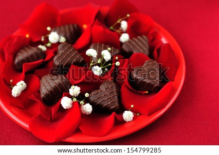 Heart-shaped chocolate candies with rose petals over red background, St. Valentine - stock photo