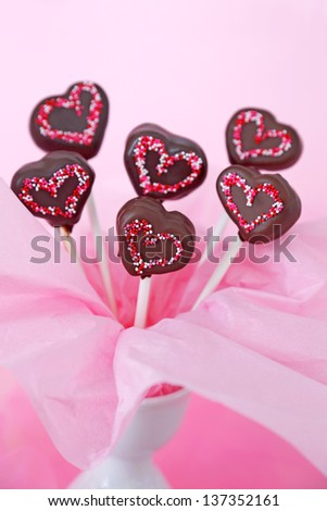 Heart shaped chocolate dipped cakepops with sprinkles on a pink background - stock photo