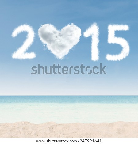 Heart shaped cloud of new year 2015 with copyspace for a text on the beach - stock photo
