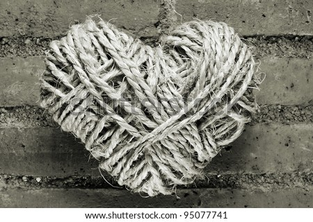 heart-shaped coil of rope on a brick wall - stock photo
