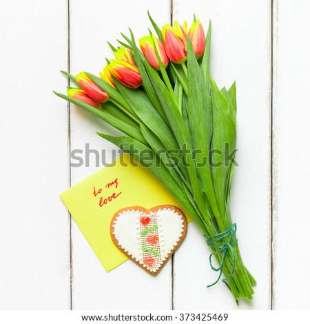 Heart shaped cookie and tulip flowers for Valentines or Mathers day - stock photo