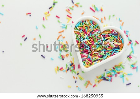 Heart shaped cookie cutter with candy sprinkles - stock photo