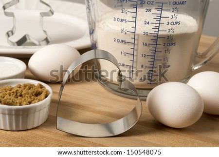 Heart shaped cookie cutter with eggs, flour, sugar and other ingredients on a wood cutting board - stock photo