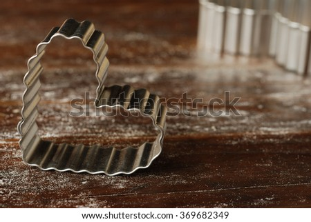 Heart shaped cookie cutters on rustic wood dusted with flour.  Closeup with shallow dof.