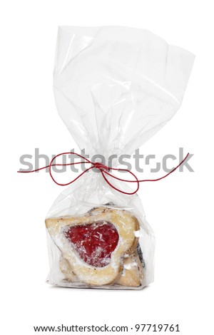 heart-shaped cookie with strawberry jam on transparent bag, isolated on white