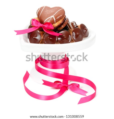 Heart-shaped cookies and chocolate pralines arranged on a white ceramic plate and decorated with pink ribbon and bows. Isolated on white - stock photo