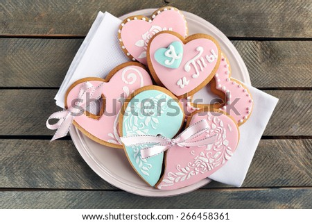 Heart shaped cookies for valentines day on plate, on wooden background - stock photo