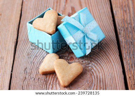 Heart shaped cookies in a blue gift box on a wooden background. Selective focus - stock photo