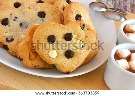 Heart shaped dark and white chocolate cookies, a sweet treat for your Valentine includes hot chocolate sprinkled with mini marshmallows - stock photo
