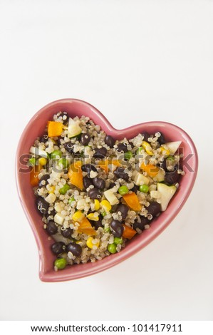 Heart shaped dish filled with quinoa and vegetable salad - stock photo