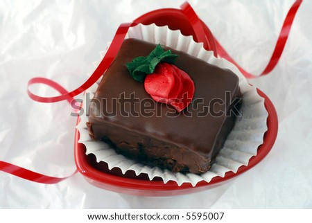 Heart shaped dish with dark chocolate petit four on white tissue paper.  Curly red ribbon added for accent.  Close-up with shallow dof. - stock photo