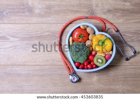 Heart shaped dish with vegetables and stethoscope isolated on wooden background - stock photo