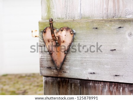 Heart shaped door handle of old garden door. - stock photo