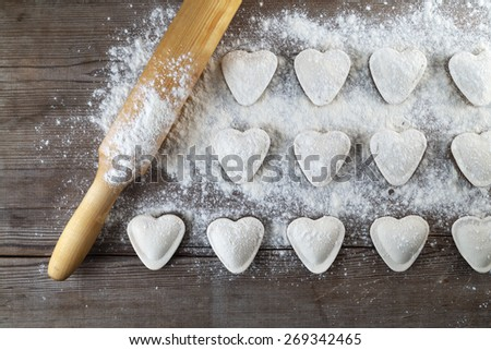 Heart shaped dumplings, flour and rolling pin on wooden background. Cooking ravioli. Top view. - stock photo