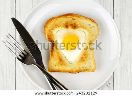 Heart shaped egg in toast for Valentines Day on white wood table    - stock photo