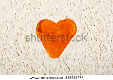 heart-shaped egg yolk in flour - stock photo