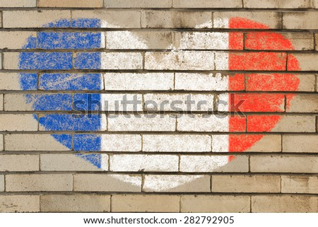 heart shaped flag in colors of France on brick wall - stock photo