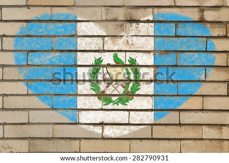 heart shaped flag in colors of guatemala on brick wall - stock photo
