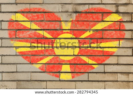 heart shaped flag in colors of macedonia on brick wall - stock photo