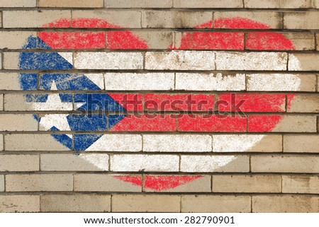 heart shaped flag in colors of puerto rico on brick wall - stock photo