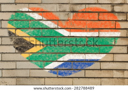 heart shaped flag in colors of South Africa on brick wall - stock photo