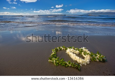 Heart shaped flower lei and leaf garland (wedding leis) on a tropical beach - stock photo