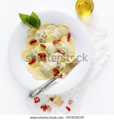 Heart shaped food. delicious ravioli. freshly homemade. cooked. in a white plate. with the basil leaves and olive oil. - stock photo