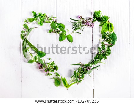 Heart shaped frame of assorted sprigs of fresh green culinary herbs arranged on a rustic white wooden background symbolic of love and romance with central copyspace