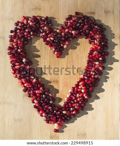 heart-shaped frame or border made of pomegranate arils (seeds) with bamboo background - stock photo