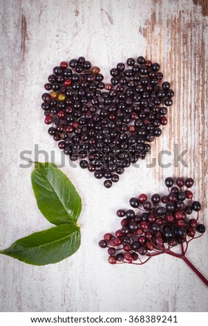Heart shaped fresh elderberry on old rustic wooden background, symbol of love, healthy nutrition, alternative medicine and therapy - stock photo