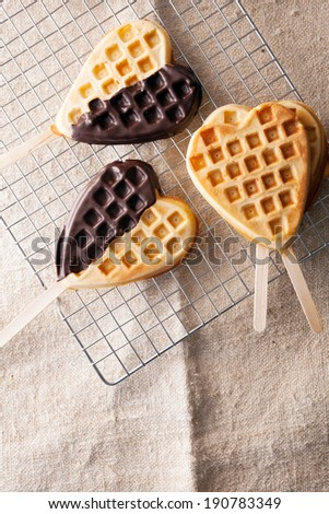 Heart-shaped freshly baked golden waffle lollipops, some with a chocolate coating on a wire mesh rack in the kitchen ready for a party or special occasion for a sweetheart or loved one - stock photo
