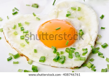 Heart shaped fried egg in the form of a heart isolated on a white background - stock photo