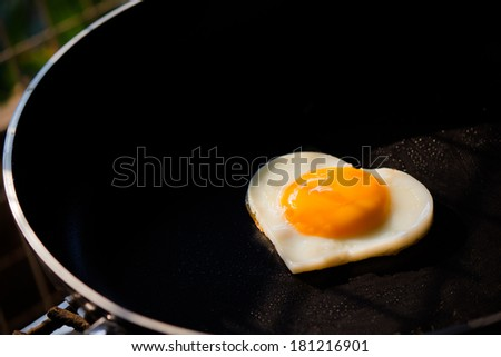 heart-shaped fried egg on frying pan - stock photo