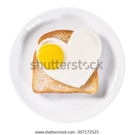 heart-shaped fried eggs and fried toast isolated on a white background - stock photo