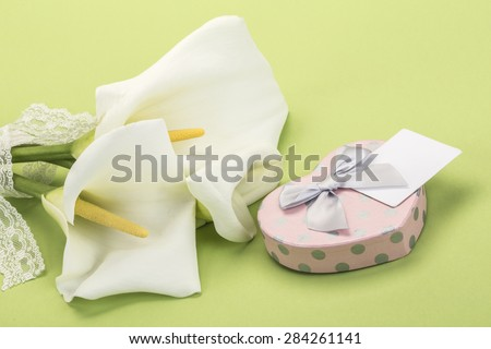 heart shaped gift and white lilly flowers on green - stock photo