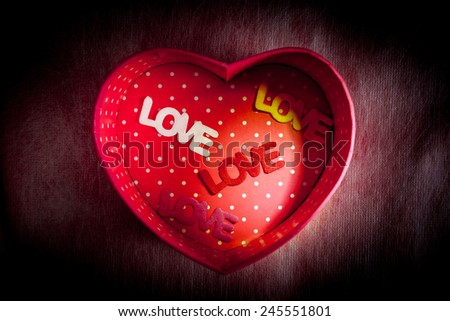 "Heart-shaped gift box and four text ""LOVE"" in box on dark background low key lighting picture style for a Valentine's day, love concept"