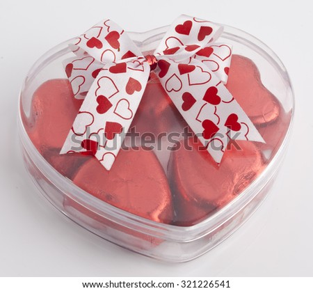 Heart shaped gift box having  Red Foil wrapped chocolate hearts - stock photo