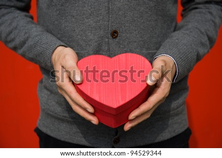 Heart shaped gift box in hands.