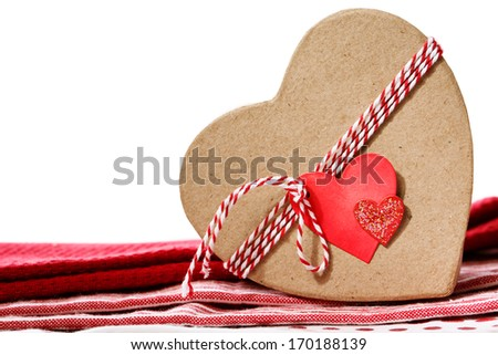 Heart shaped gift box with heart tag on red table cloth - stock photo