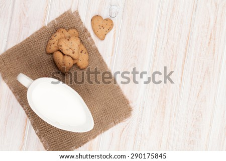 Heart shaped gingerbread cookies and milk pitcher. On white wooden table - stock photo