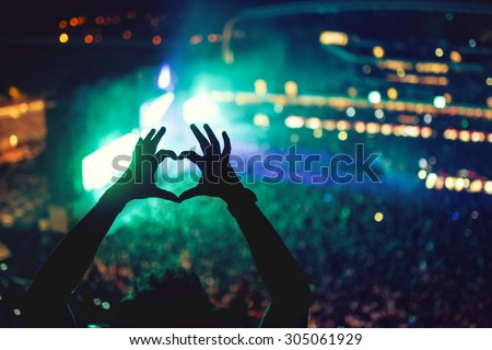 Heart shaped hands at concert, loving the artist and the festival. Music concert with lights and silhouette of a man enjoying the concert - stock photo